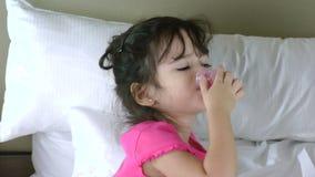 Menina na cama que toma a medicina video estoque