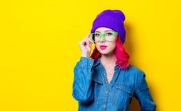 Menina na camisa azul, no chapéu roxo e em vidros verdes Fotografia de Stock Royalty Free