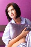 Menina na camisa de um homem que senta-se em uma cama com descanso Fotografia de Stock