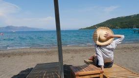 Menina na camisa e no chapéu que sentam-se na praia no sunbed sob um guarda-chuva filme