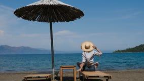 Menina na camisa e no chapéu que sentam-se na praia no sunbed sob um guarda-chuva video estoque