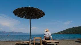 Menina na camisa e no chapéu que sentam-se na praia no sunbed sob um guarda-chuva vídeos de arquivo