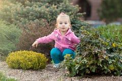 Menina na camiseta cor-de-rosa que senta-se nos arbustos Imagens de Stock Royalty Free
