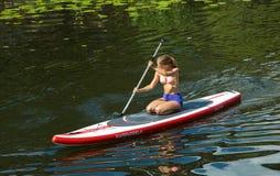 Menina na canoa que rema em um canal na cidade Imagens de Stock