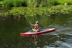 Menina na canoa que rema em um canal na cidade Foto de Stock Royalty Free