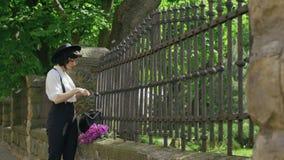 A menina na cerca sai dos vidros do saco, veste-os e corrige-ao chapéu filme