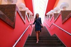 A menina na cidade na menina do escalatorThe vai abaixo das escadas nas paredes vermelhas bonitas da sala imagens de stock