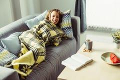 Menina na cobertura que relaxa no sofá na sala de visitas Imagens de Stock