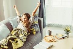 Menina na cobertura que relaxa no sofá na sala de visitas Imagem de Stock Royalty Free