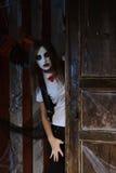 A menina na composição olha atrás da porta fotos de stock