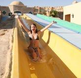 Menina na corrediça de água da piscina Imagens de Stock Royalty Free