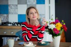 Menina na cozinha com o copo no tempo de café da manhã foto de stock