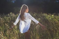 Menina na dança branca da camisa no campo imagens de stock royalty free