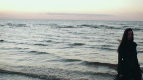 Menina na dança escura do cabelo da agitação do vestido na água na costa Photoshoot modelo Sea video estoque