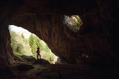 Menina na entrada de uma caverna fotos de stock royalty free