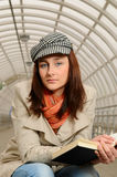 A menina na estação leu um livro Imagens de Stock Royalty Free