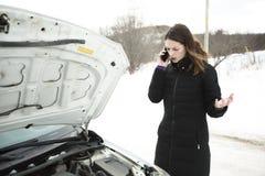 A menina na estrada do inverno está chamando o telefone perto do carro foto de stock royalty free