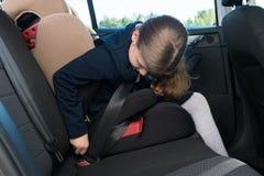 A menina na farda da escola prende um cinto de segurança ao sentar-se em um banco de carro das crianças fotografia de stock royalty free