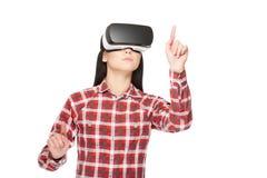 A menina na fatura dos auriculares de VR escolhe e em apontar pelos dedos imagem de stock