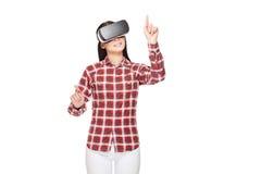 A menina na fatura dos auriculares de VR escolhe e em apontar pelos dedos foto de stock royalty free