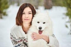 Menina na floresta do inverno que anda com um cão A neve está caindo foto de stock