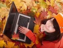 Menina na folha alaranjada do outono com portátil. foto de stock royalty free