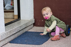 Menina na frente da porta Fotos de Stock