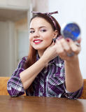 Menina na frente do espelho que tenta em brincos Imagens de Stock
