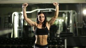 Menina na ginástica Treinamento do peso Trabalho nos músculos da parte traseira bodybuilding video estoque
