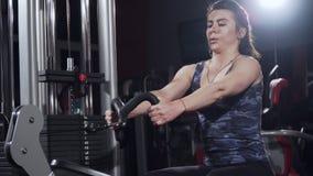 Menina na ginástica Treinamento do peso Trabalho nos músculos da parte traseira Mulheres que dão certo na máquina de enfileiramen filme
