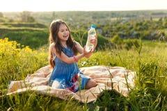 Menina na grama com garrafa de água plástica Fotos de Stock