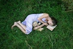 Menina na grama com livro Imagens de Stock Royalty Free