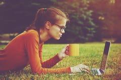 Menina na grama usando a datilografia do portátil Foto de Stock Royalty Free