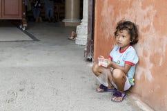 A menina na idade macia aprende o comércio do mendigo no portal da porta da jarda da igreja procurar a esmola imagens de stock royalty free