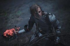 A menina na imagem do arco do ` de Jeanne d na armadura e com a espada em suas mãos ajoelha-se contra o fundo do fogo e do fumo imagens de stock