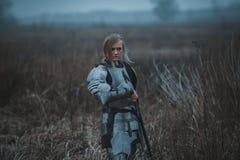 A menina na imagem do arco do ` de Jeanne d na armadura e com a espada em suas mãos está no prado Vista traseira imagem de stock royalty free