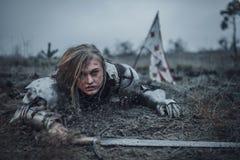 A menina na imagem do arco do ` de Jeanne d na armadura rasteja na lama com a espada em suas mãos no fundo da bandeira imagens de stock royalty free