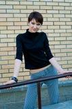 Menina na ligação em ponte preta e em calças listradas Foto de Stock