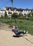 Menina na linha corrediça de Tirol que tem o divertimento fotografia de stock royalty free