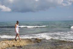 Menina na linha costeira rochosa Fotografia de Stock