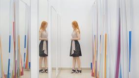 A menina na loja de roupa escolhe o vestido perto do espelho em sala apropriada - conceito da compra Imagem de Stock