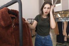 A menina na loja de roupa escolhe um casaco de pele novo foto de stock