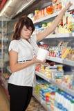 A menina na loja escolhe a maionese fotos de stock