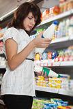 A menina na loja escolhe o leite Foto de Stock Royalty Free
