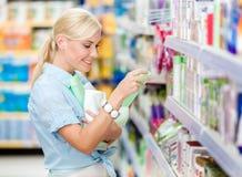 Menina na loja que compra cosméticos Imagens de Stock Royalty Free