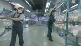 A menina na máscara das combinações conduz a cremalheira com as bobinas da fibra de vidro ao longo da oficina vídeos de arquivo