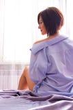A menina na manhã senta-se na cama Fotografia de Stock