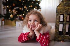 Menina na mentira vermelha da camiseta sob a árvore de Natal e na espera para um milagre fotografia de stock royalty free