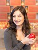 Menina na mercearia que guarda uma maçã vermelha ao sorrir fotografia de stock royalty free