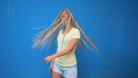 A menina na moda do moderno que agita a trançou as tranças do cabelo e o giro ao redor no fundo azul vídeos de arquivo